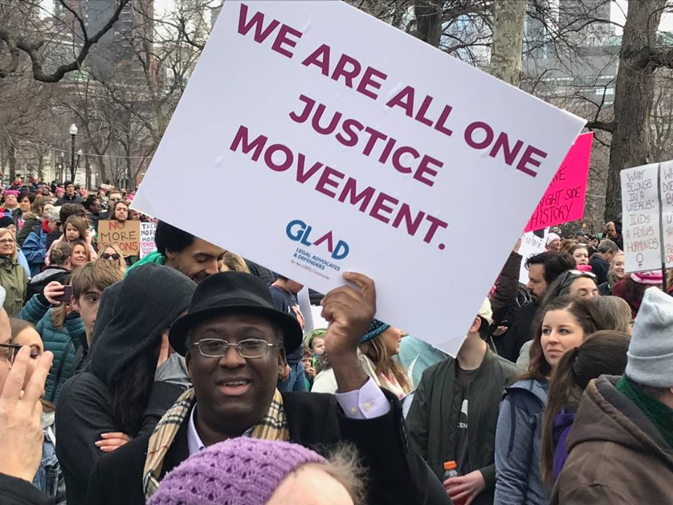 A man holding a sign at a rally reading We are all one justice movement