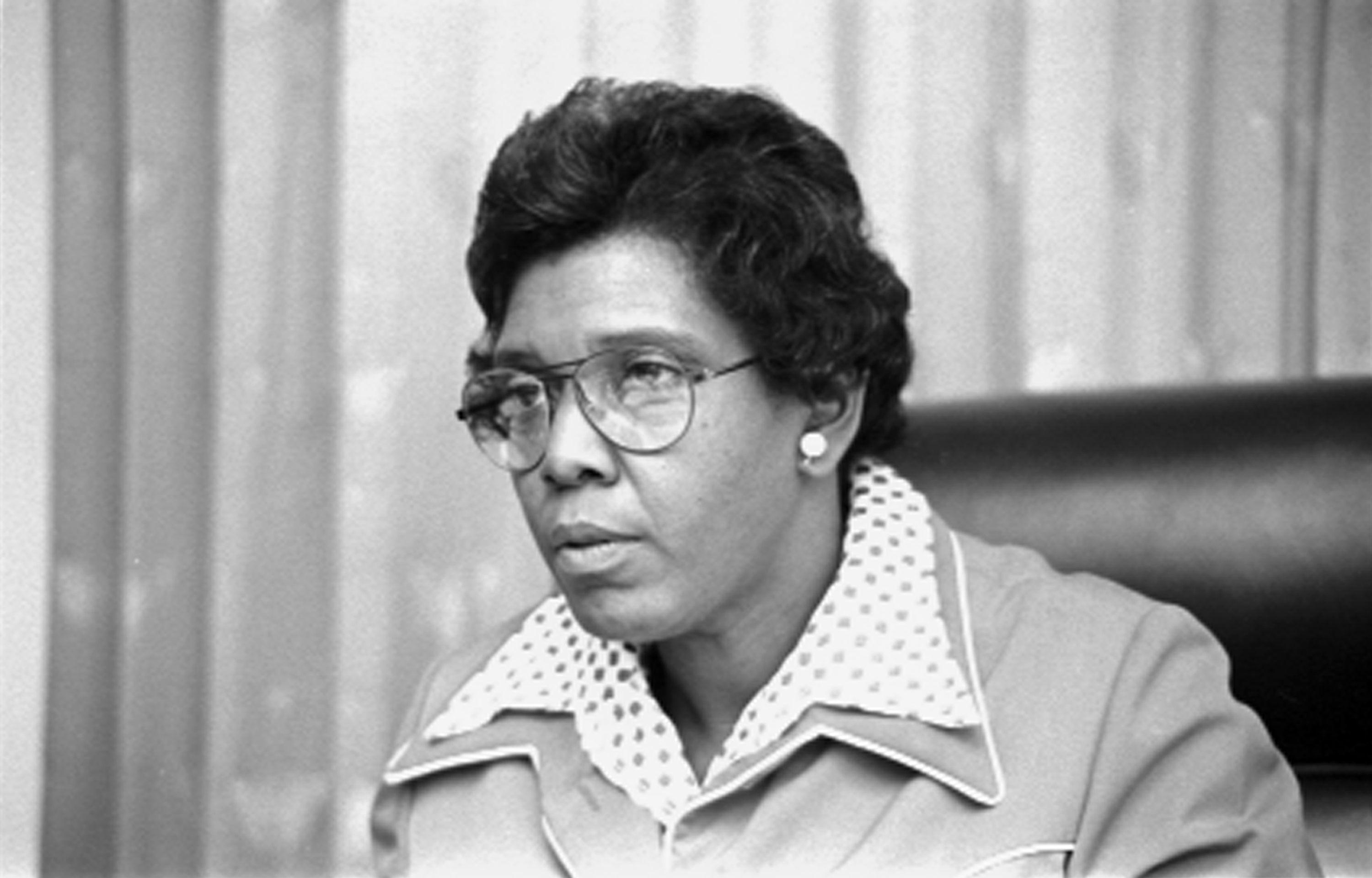 Image: Black and white photo of Jordan sitting in a leather chair speaking from behind a desk. She is wearing glasses.