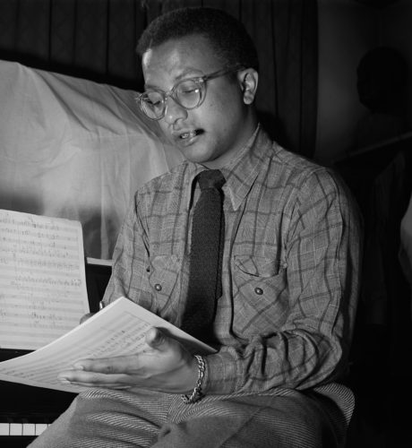 [Image: Black and white photo of Strayhorn sitting in front of a piano looking at sheet music. He is wearing glasses and has a small cigar in his mouth.]
