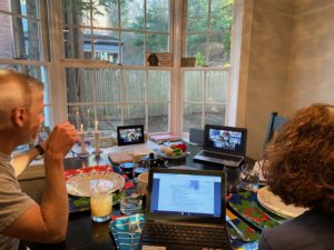 Two people sit at seder table in front of three laptops, each displaying Zoom call participants