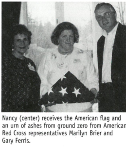 "Photo of Nancy holding folded American flag with text: ""Nancy (center) receives the American flag and an urn of ashes from ground zero form American Red Cross representatives Marilyn Brier and Gary Ferris"