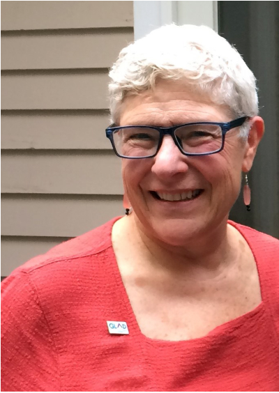 Joyce Kauffman, short silver hair, rectangular glasses, coral shirt