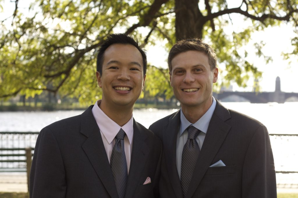 ED Janson Wu photo from wedding. Husband on right, suits and ties outside in beautiful weather with leafy trees behind.