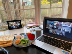 Two laptops on a seder table, each displaying Zoom calls with multiple people