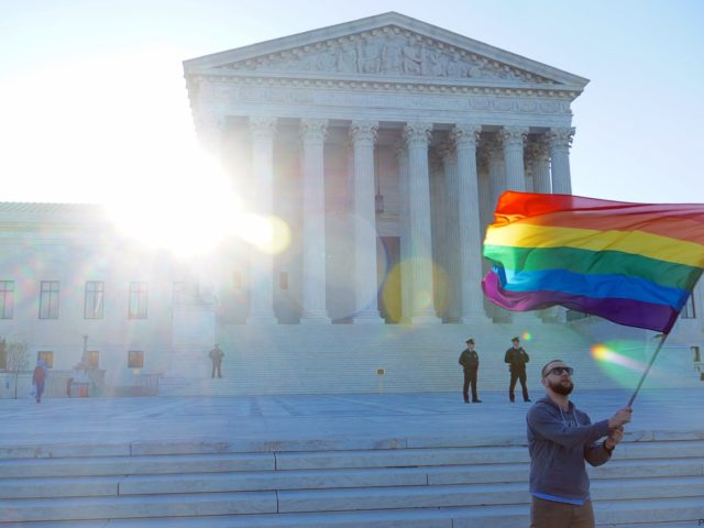 Person holding rainbow Pride flag in front of U.S. Supreme Court building.