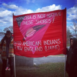 Two UAINE members holding sign that says: Homophobia is not native to these shores! United American Indians of New England (UAINE).