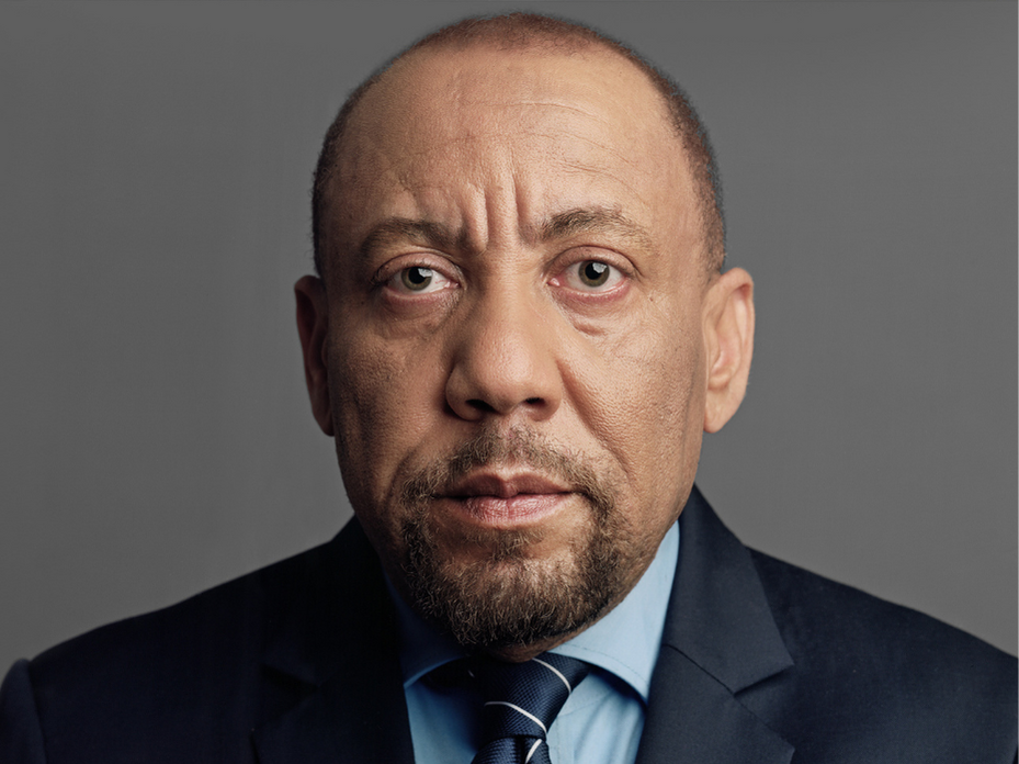Close-up of Kylar Broadus in navy suit with a blue shirt and tie, serious expression, looking directly into the camera.